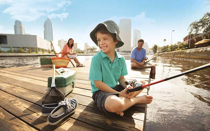Family fishes off dock on Hillsborough River near downtown Tampa, Florida