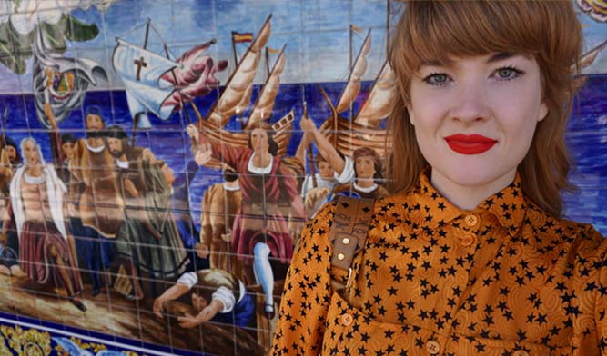 Influencer Emmy Wildwood stands in front of a tile mural in Ybor City in Tampa Florida wearing an orange shirt with stars