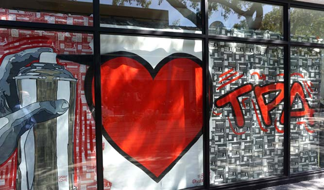 A Tampa, Florida storefront shows a mural with a large spray paint can, a red heart and the letters TPA.