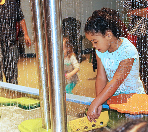 Science and fun collide at the Clay Center for the Arts and Sciences as a little girl plays at the water station.