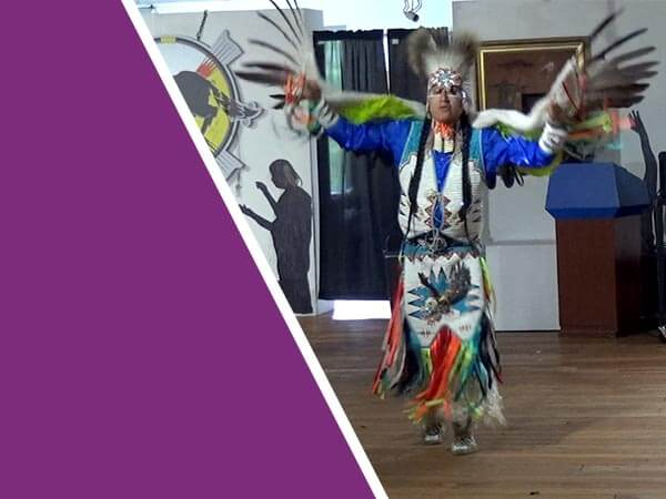 A Native American performing a dance at the Trickster Gallery