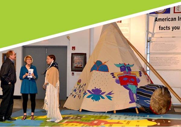 Two visitors to the Trickster Gallery talk with an expert next to a tipi