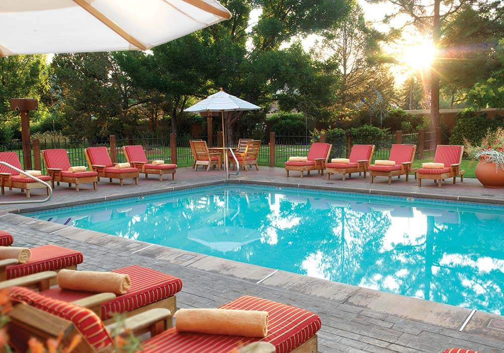 A sparkling swimming pool with plenty of lounge chairs at the Inn and Spa at Loretto.