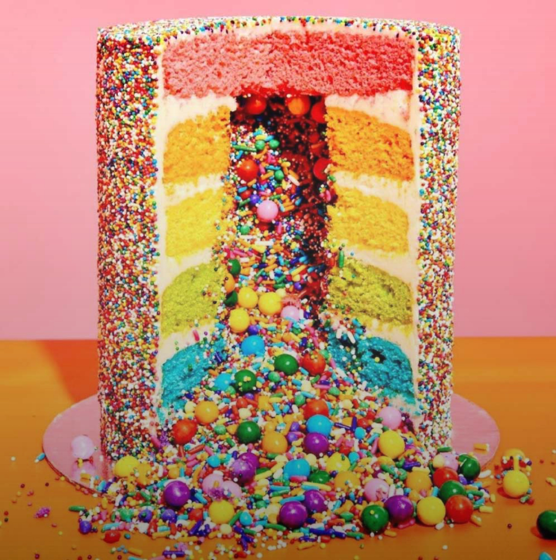 A colorful six-layer cake covered with colorful sprinkles with a slice cut out and colorful candies and sprinkles spilling out of the middle from the Flour Shop in Beverly Hills, CA.