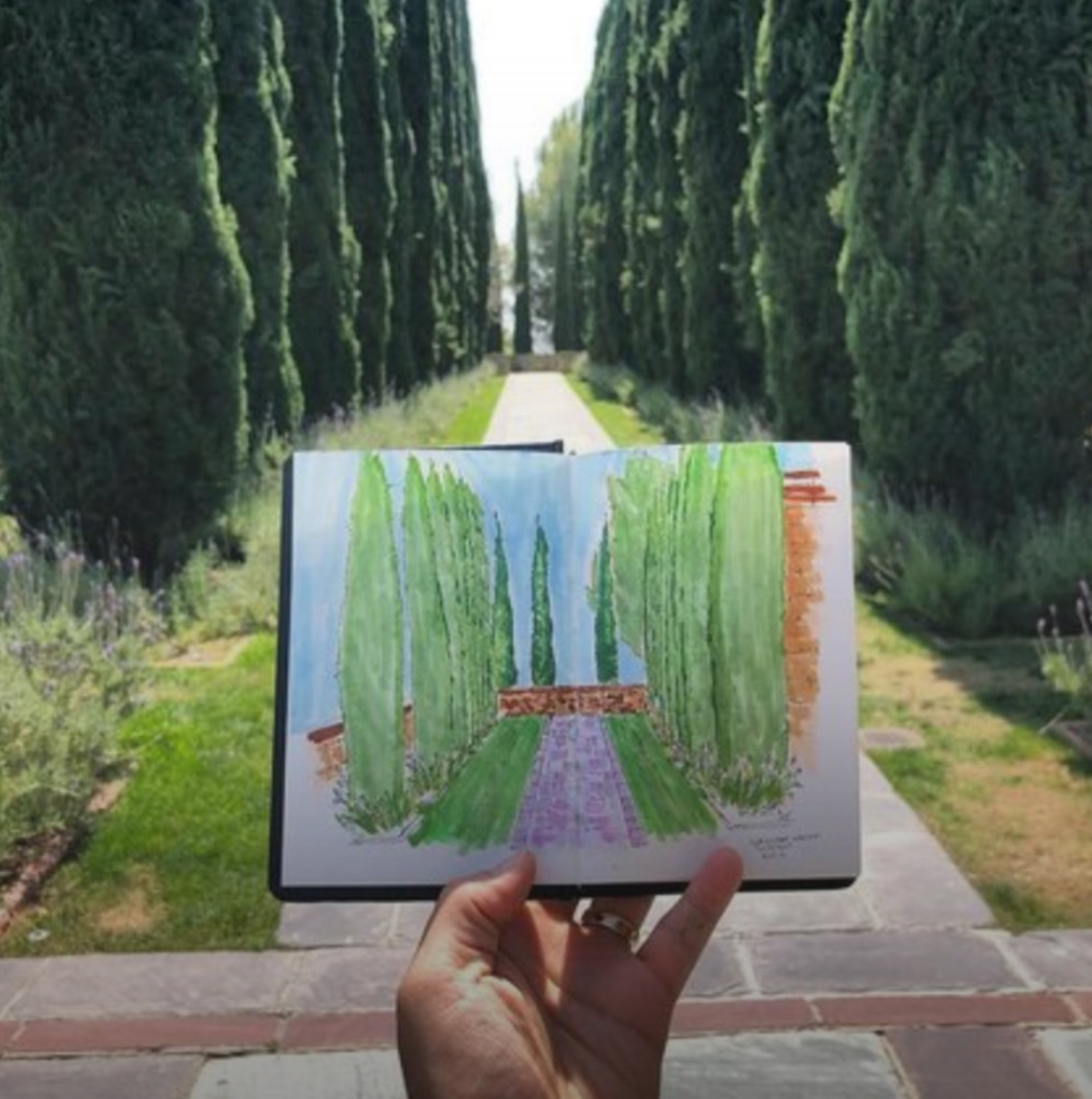A hand holds a small painting of a landscape from Greystone Mansion in Beverly Hills, CA, with the scene behind it. Instagram photo by @feetfingerseyes