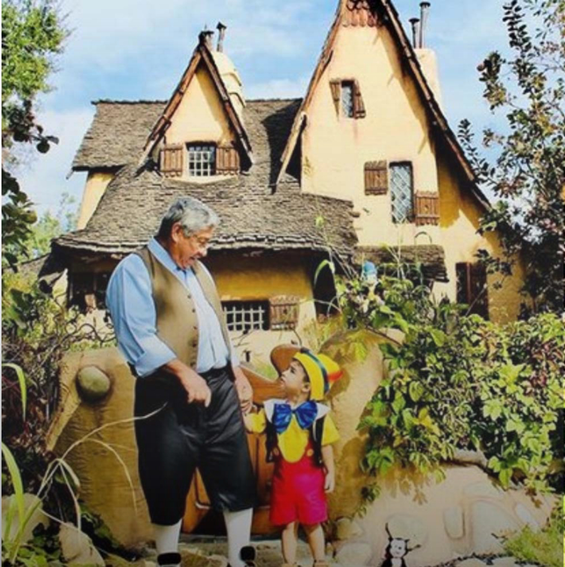 A small boy dressed up like Pinnocchio holds hands with an old man dressed like Gepetto at Gepetto's house in Disneyland in California. Instagram photo of the Spadena House by @mrsaguilarmarquez