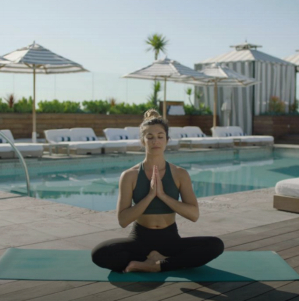 A woman in a yoga outfit meditates with hands in prayer pose poolside at in Beverly Hills, CA.