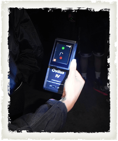A hand holds an Ovilus IV device for detecting paranormal activity