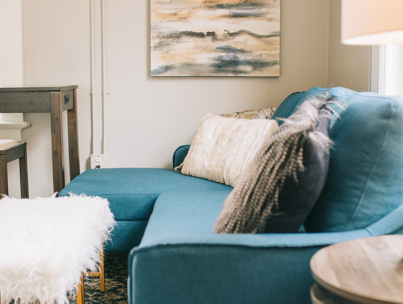 A close up of a seating area with blue sofa and fuzzy pillows and a fuzzy white table topper at the newly reopened historic Blanche hotel in Lake City, Florida.