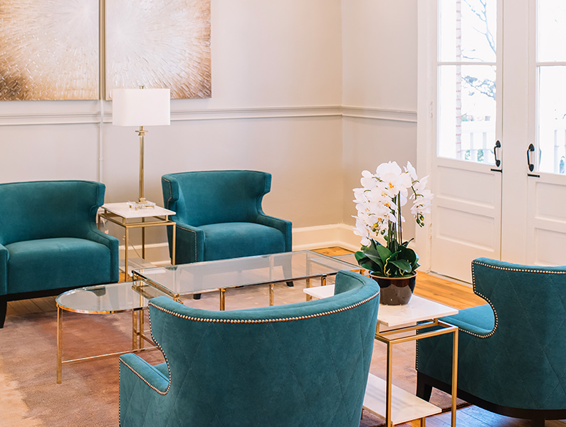 A modern seating area with aquamarine blue suede chairs and glass topped tables with a potted blooming white orchid at The Blanche hotel in Lake City, Florida, which recently reopened after a major renovation.