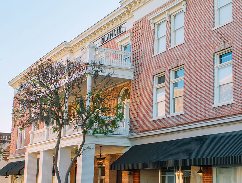 A street view of the white brick pillared entrance and restored balconies at the Blanche, a historic hotel recently renovated and reopened with new office, retail, co-working spaces and apartments in Lake City, Florida.