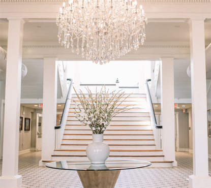 The lobby of the historic Blanche hotel looking up at the grand staircase, with its white columns and crown molding and polished hardwood steps and centerpiece chandelier in Lake City, Florida.