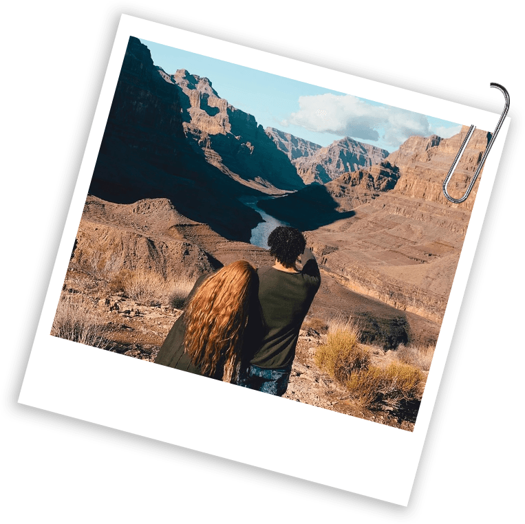 A photograph shows a man and a woman from behind as they look over the Grand Canyon