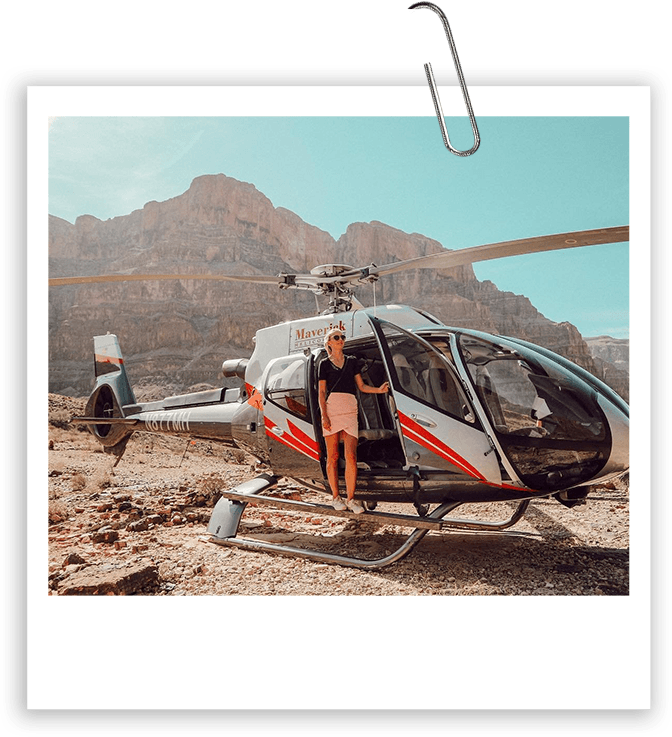 A woman wearing sunglasses stands in the open door of a helicopter on the ground at the Grand Canyon