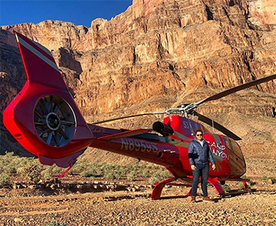 A young woman lies on her back on the Skywalk, with the Grand Canyon visible below her;  A man stands next to a red helicopter at the Grand Canyon