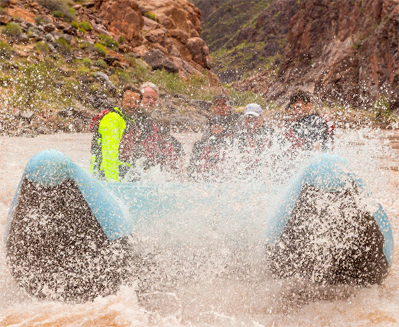 A group of people ride on a raft with Hualapai River Runners at the Grand Canyon, as water sprays up around their raft