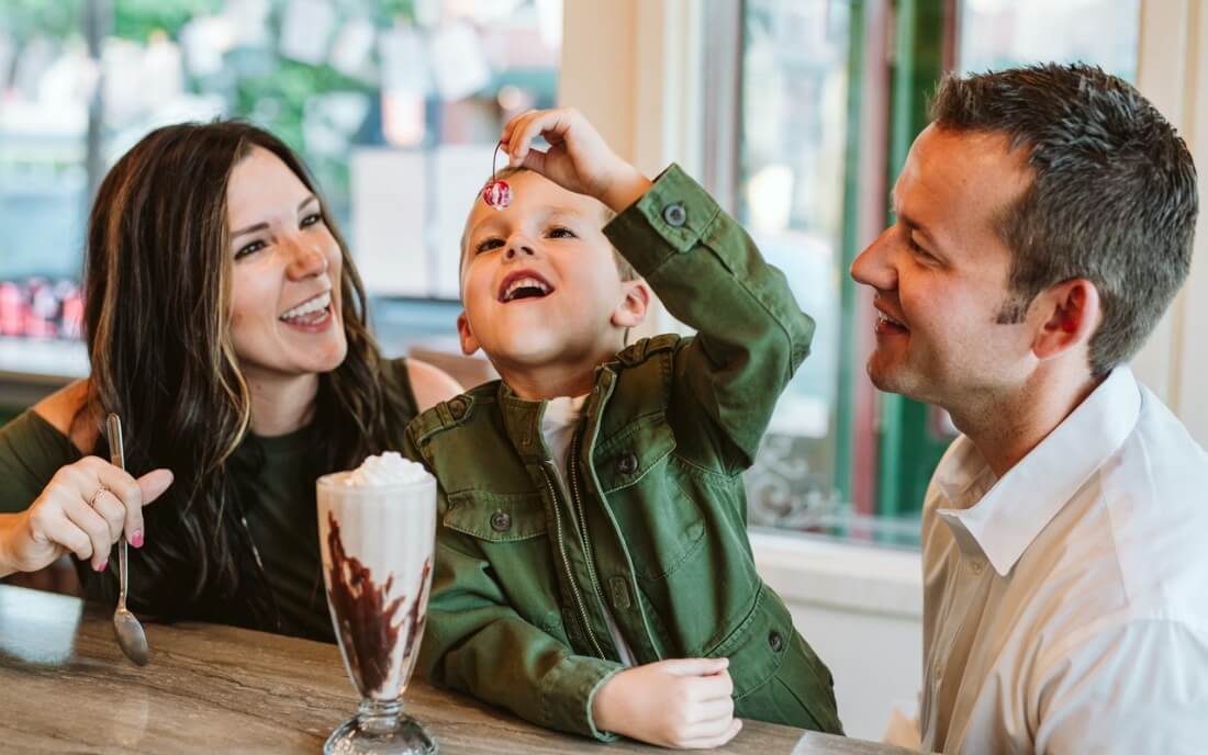 Parents and their son enjoy an ice cream sundae at Clinton's Soda Fountain in Independence, MO