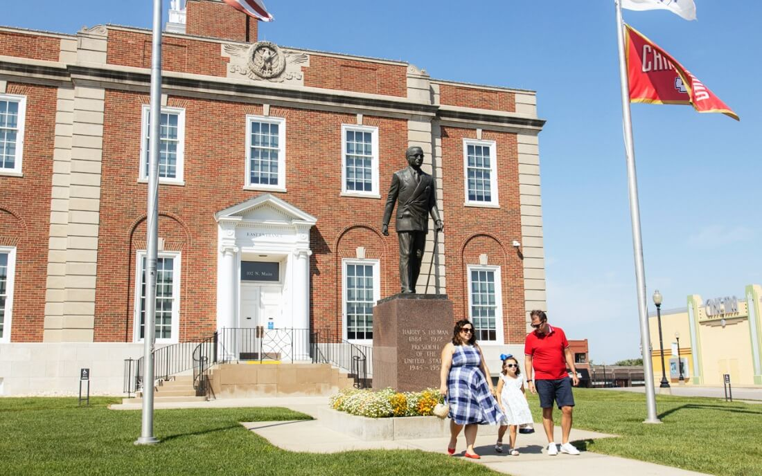 Influencer Jen Cowan and her family in front of the Harry S. Truman statue on the Historic Independence Square in Independence, MO