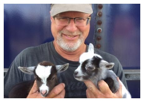 A man wearing a baseball cap holds two baby goats at Akerman Family Farms near Peoria, Illinois