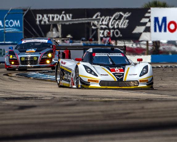 Two race cars head into a turn at Sebring International Raceway, in Sebring, Florida.