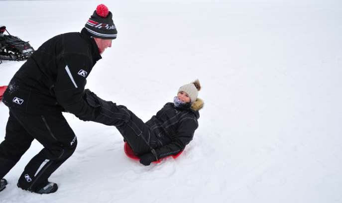 Father pushes kid on sled in St. Germain.