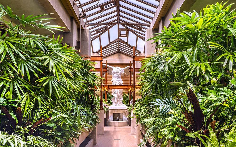 """Frank Lloyd Wright's Martin House Complex in Buffalo features a beautiful conservatory with a replica statue of """"Winged Victory."""""""
