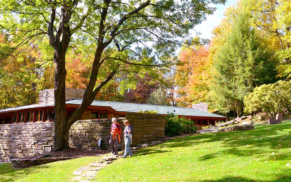 Situated just below the crest of a hill, Kentuck Knob's construction materials of native sandstone and tidewater red cypress blend naturally with the surroundings.