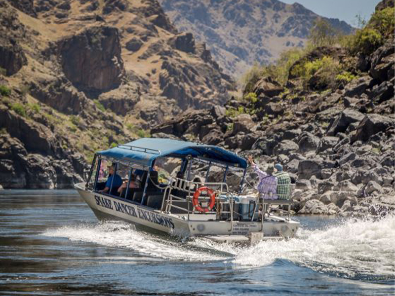 A jet boat with a blue awning splashes through the Snake River in Hells Canyon while two people ride at the rear, waving.