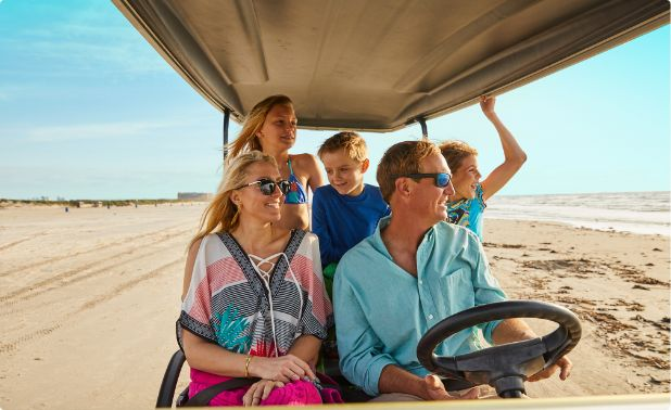 A family driving along the beach in Port Aransas, Texas.