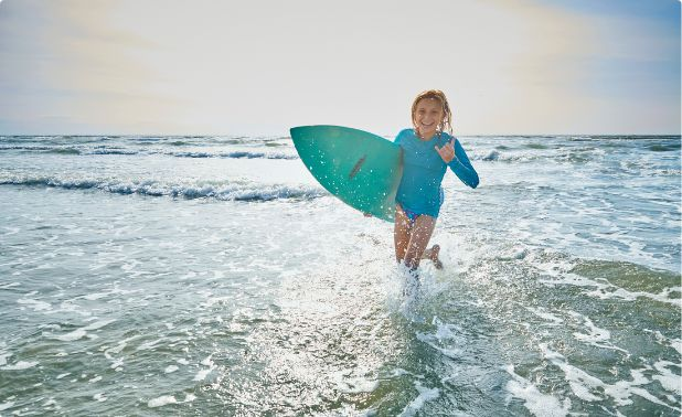A young girl runs back ashore with her surfboard and smile.