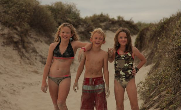 Kids smiling after playing in the sand in Port Aransas, Texas.