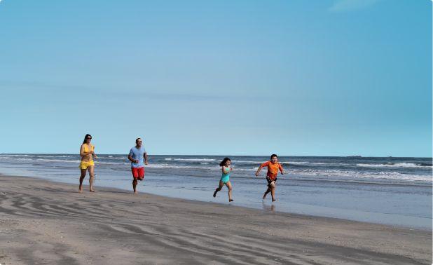 A family runs along the beach in Port Aransas, Texas.