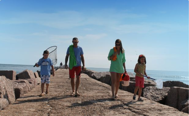 A family walks along the jetty having finished their fishing trip in Port Aransas.