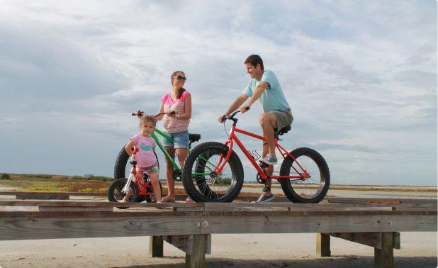 A family biking along a wooden bike trail in Port Aransas.