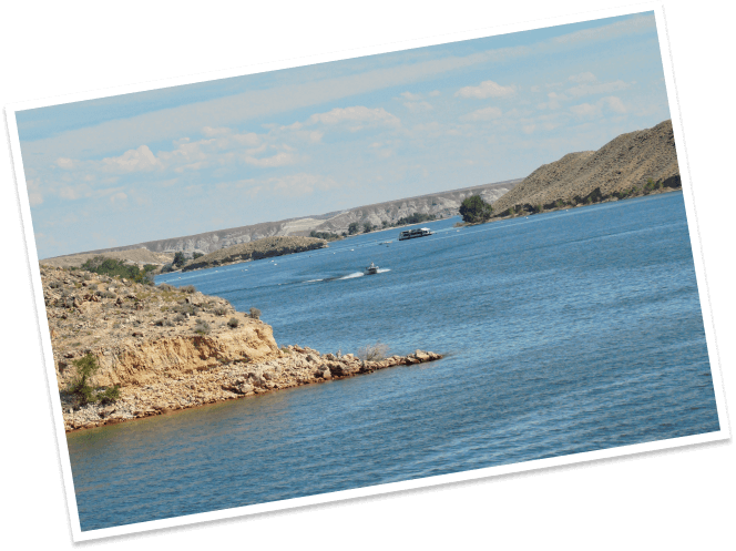 Boats ride across the placid waters of the Boysin Reservoir near Shoshoni, Wyoming.